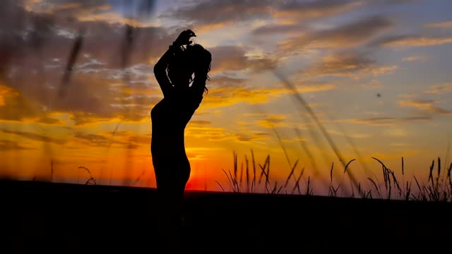 beautiful girl her arms standing in a field at sunset slow motion video video