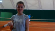 Beautiful girl holding a tennis racket and smiling on the court video