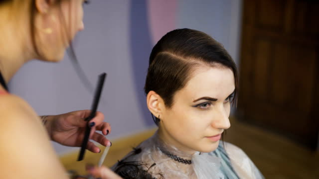 Beautiful girl in a beauty salon. Professional stylist makes to the woman a new stylish haircut video