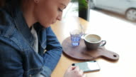 Beautiful girl in a coffee shop reading on her smart phone. video