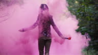 Beautiful girl in a forest spins around while holding a pink smoke grenade, slow motion video