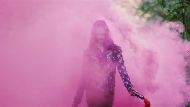 Beautiful girl in a forest waves around a pink smoke grenade and then tosses it behind her, slow motion video