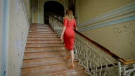 Beautiful girl in a red dress goes up the stairs video
