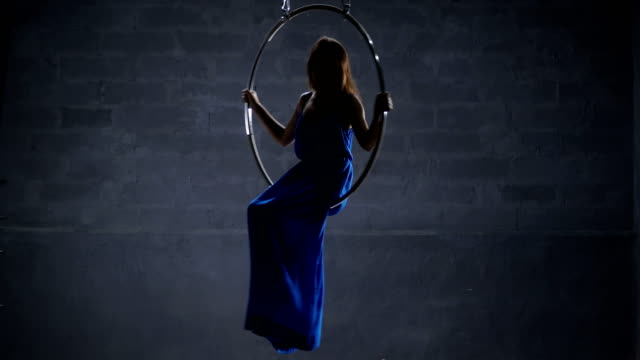 Beautiful girl in blue dress is spinning in the aerial hoop video