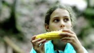 Beautiful girl in blue jacket eats corn and looks around video