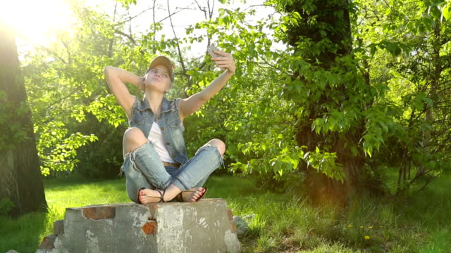 Beautiful girl in jeans clothes making selfie on the phone in the Park. video