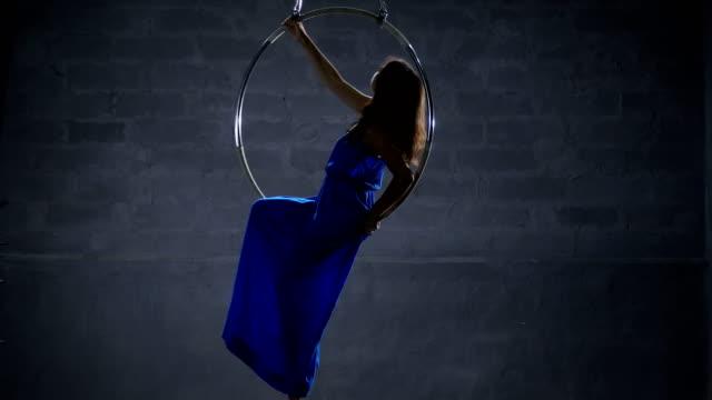 Beautiful girl in long blue dress in the aerial hoop video
