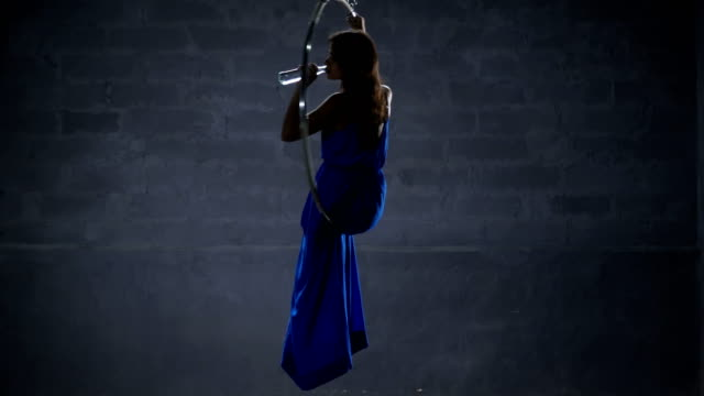 Beautiful girl in long dress drinks water in the aerial hoop video