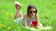 Beautiful girl in sunglasses with red smartphone lies on green grass video
