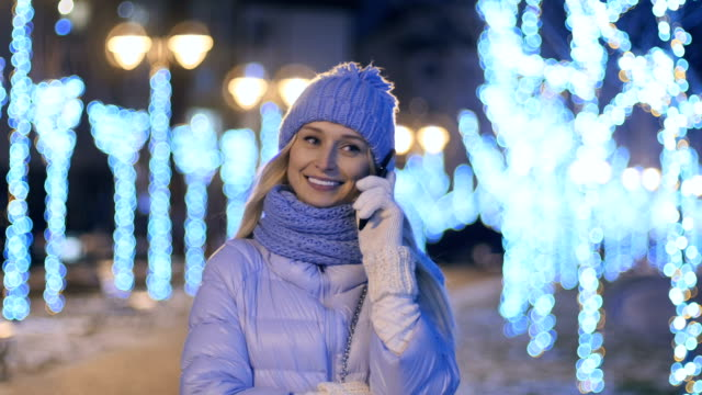 Beautiful girl in winter cloth talks on the telephone at night lights background video