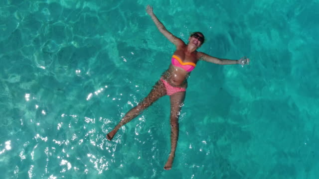 Beautiful girl is laying in clear blue water of Maldivian lagoon video