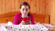 Beautiful girl lies on the bed and communicates via smartphone video