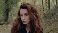 Beautiful girl looking coquettishly in forest video