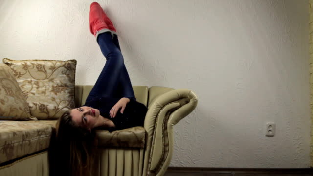 Beautiful girl lying relaxed on the couch upside down, legs up video