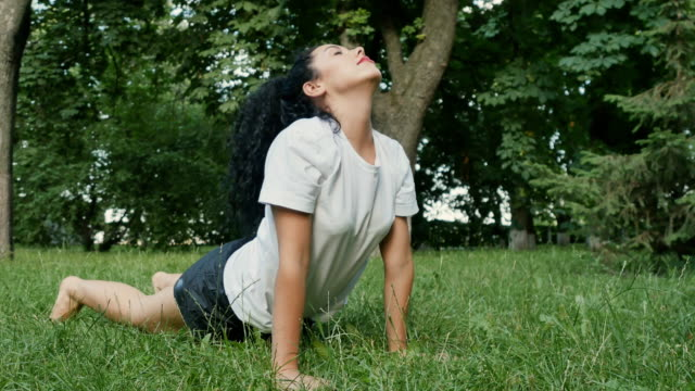 Beautiful girl makes stretching exercises on grass in park video