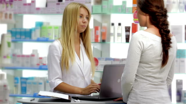 Beautiful girl pharmacist consulting a customer video
