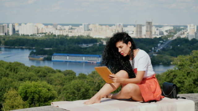 Beautiful girl relax with tablet at city background video