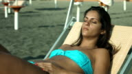 beautiful girl relaxing in the sun on the beach by the sea: summer, tan video