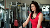Beautiful girl rides a bicycle in a gym video