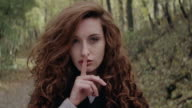 Beautiful girl showing silence sign in forest video