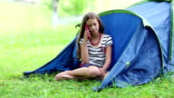 Beautiful girl sits on a grass near tourist tent and speaks on mobile phone video