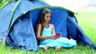 Beautiful girl sits on grass near tourist tent and uses smartphone video