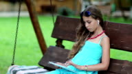 Beautiful girl sits on swing bench and holds in hands tablet computer video