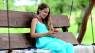 Beautiful girl sits on the swing bench in garden and speaks via smartphone video