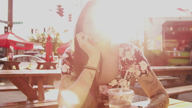 A beautiful girl sitting at an outdoor table in beautiful light with lens flare, slow motion video