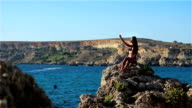 Beautiful girl sunning on a high cliff by the sea and taking selfie video