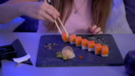 Beautiful girl take a piece of sushi with chopsticks, smiling and show a thumb video