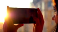 Beautiful girl taken pictures Of City With blurred architectures on background at home window in slow motion video