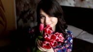 beautiful girl to sniff flowers, looking at the camera, smiling, flirting. video