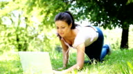 Beautiful girl typing on laptop in the green park. video
