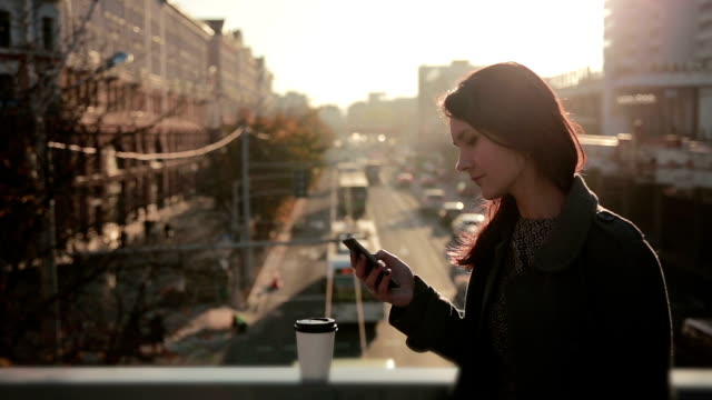 beautiful girl uses a smartphone on a city bridge video