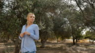 Beautiful girl walking along the plantation with olive trees video