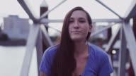 A beautiful girl walking up a dock ramp toward the camera, slow motion video