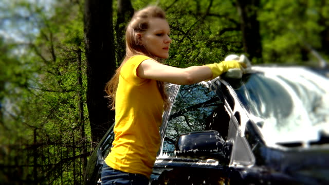 Beautiful girl washes her car with sponge. video