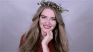 Beautiful girl wearing christmas wreath over white background. video
