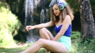 Beautiful girl with curly hair by the waterfall video