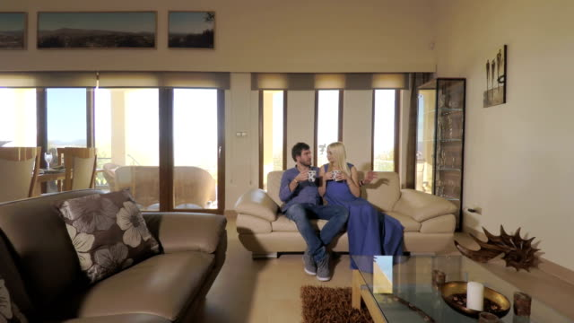 Beautiful girl with her boyfriend relaxing on the sofa in room video