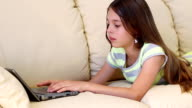 Beautiful girl with laptop on the sofa. video