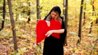 Beautiful girl with red angel wings in forest video