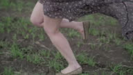 beautiful girl with ribbon in dark dress with floral print run across the green field and wind blowing her hair camera follow from shoes to face ungraded flat color  close shot video