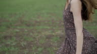 beautiful girl with ribbon in dark dress with floral print run across the green field while wind blowing her hair camera rotate follow from shoes to hair middle shot ungraded flat color video