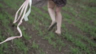 beautiful girl with ribbon in dark dress with floral print run across the green field while wind blowing her hair camera rotate follow from shoes to hair middle rear shot ungraded flat color video