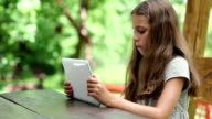 Beautiful girl with white tablet computer sits at the table video