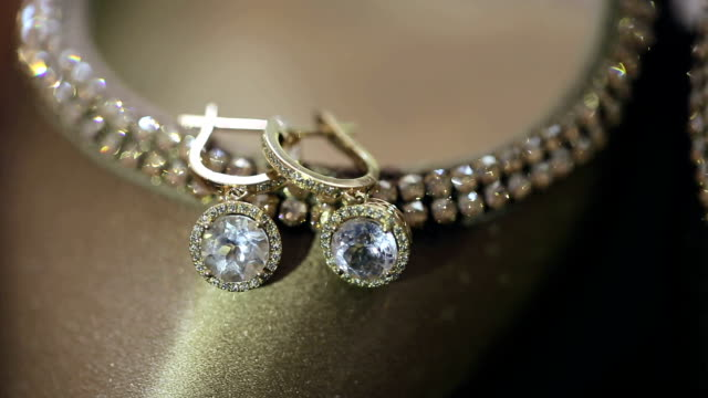Beautiful gold earrings with diamonds. Close up video