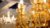 Beautiful golden color crystal chandelier illuminates all around warm amber ligh video