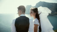 beautiful  gorgeous bride  and stylish groom kissing on rocks video